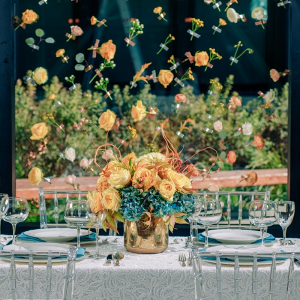 Orange and teal wedding tablescape with flower backdrop