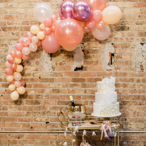 Modern white and gold wedding cake with balloon garland backdrop