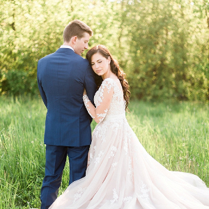 Wedding portrait with bride in long sleeve blush lace gown