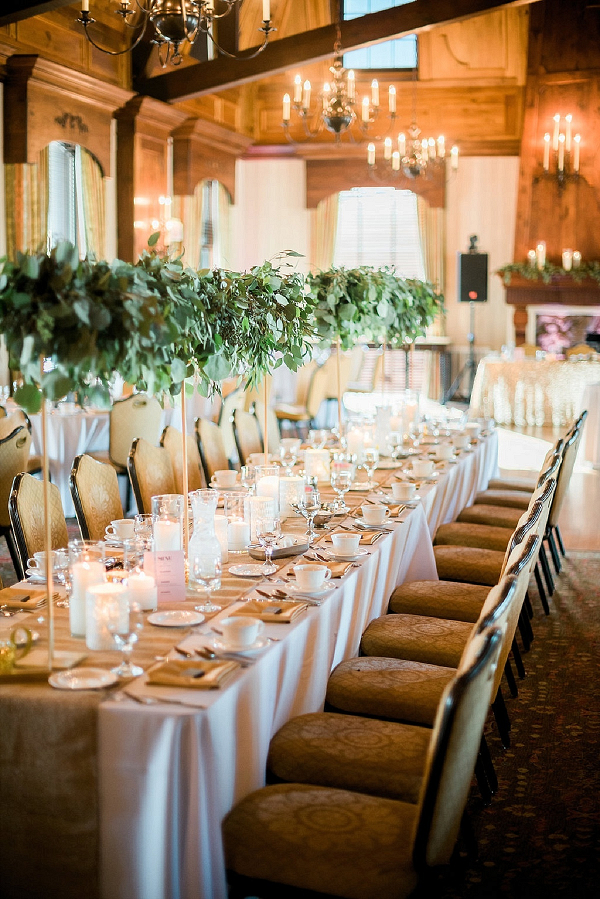 Wedding reception with tall greenery centerpieces