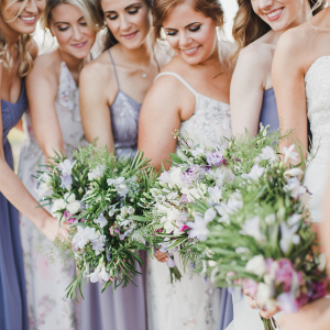 Bridesmaids in mismatched purple and lavender dresses