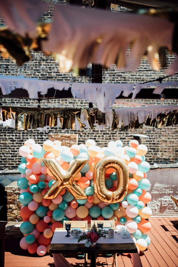 Modern rooftop wedding with balloon backdrop