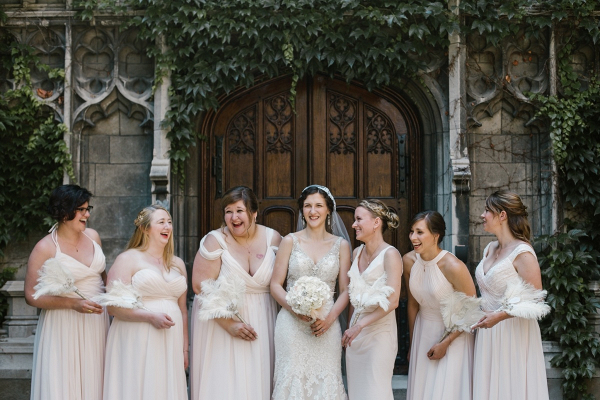 Bridal party in light blush gowns and feather fans