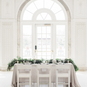 White and gray wedding table with long greenery runner