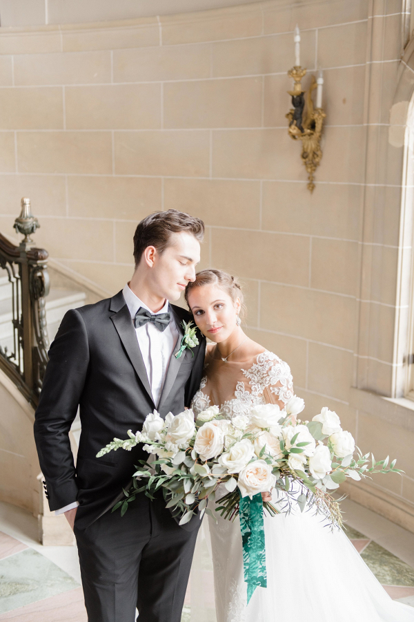 Elegant bride and groom in white, emerald green, and black