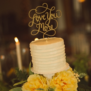 White tiered wedding cake with cake topper