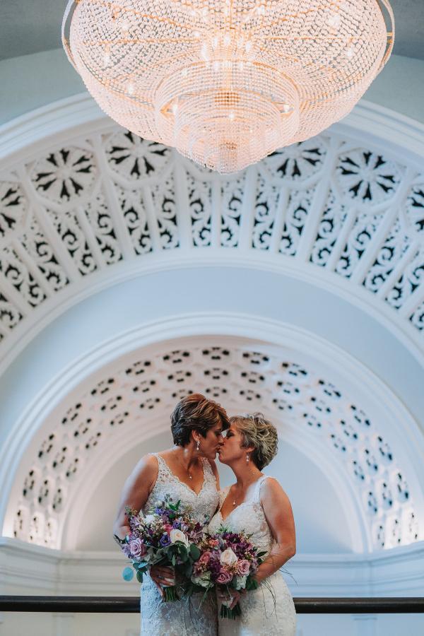 Brides under chandelier