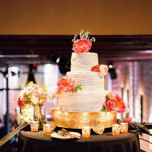 Three Tiered, Round White Wedding Cake with Coral Flower Accents on Gold Cake Stand