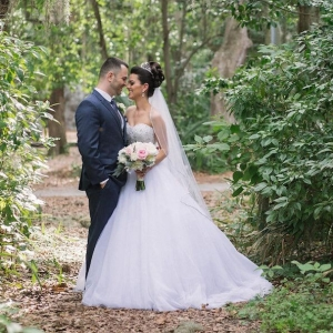 Bride in Strapless Wedding Ball Gown & Groom Wedding Portrait with Lush Greenery Backdrop