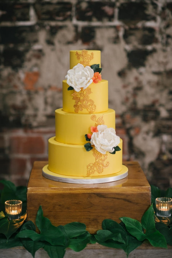 Caribbean Inspired, 4- Tiered Round Wedding Cake on Wooden Table with Yellow Fondant and Gold Design Detailing Accented with White Flowers