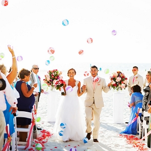 Beach, Outdoor Wedding Ceremony, Bride and Groom Walking down Aisle and Guests Throwing Beachballs