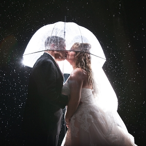 Bride and Groom Nighttime Wedding Portrait in the Rain with Umbrella