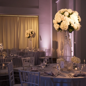 Wedding Reception Table Decor with Tall, Crystal Centerpieces with White Flowers and Crystals and White Chiavari Chairs | Pinspotting and Pink Uplighting