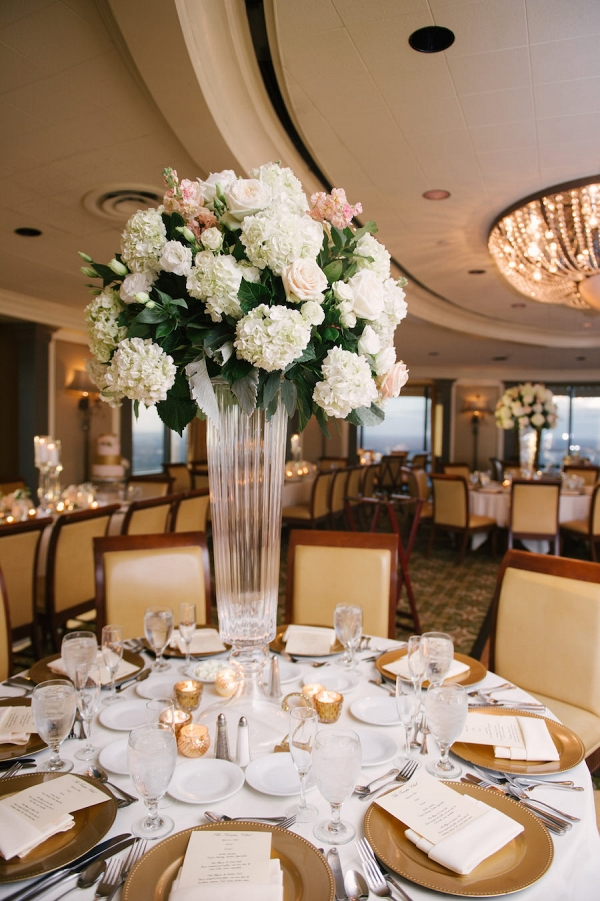 Elegant Indoor Tampa Wedding Venue with Tall Centerpieces with Hydrangeas and Roses and Chandeliers with Gold Charger Plates