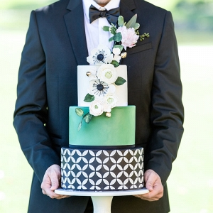 Groom Holding Green, Black and Silver Modern Geometric Wedding Cake with Sugar Flowers
