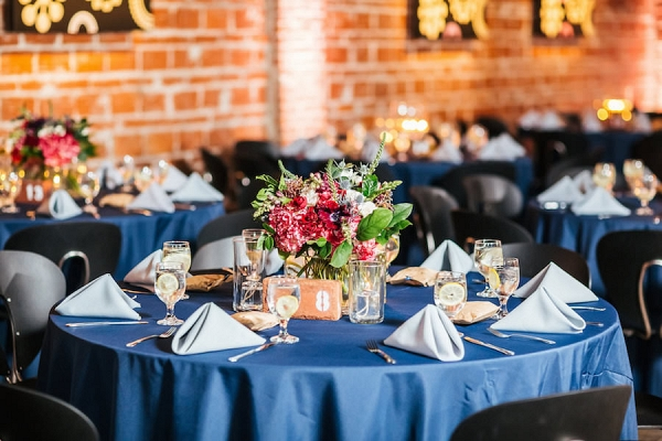 Merlot Red and White Wedding Centerpieces with Greenery and Blue Linen with Brick Venue Walls