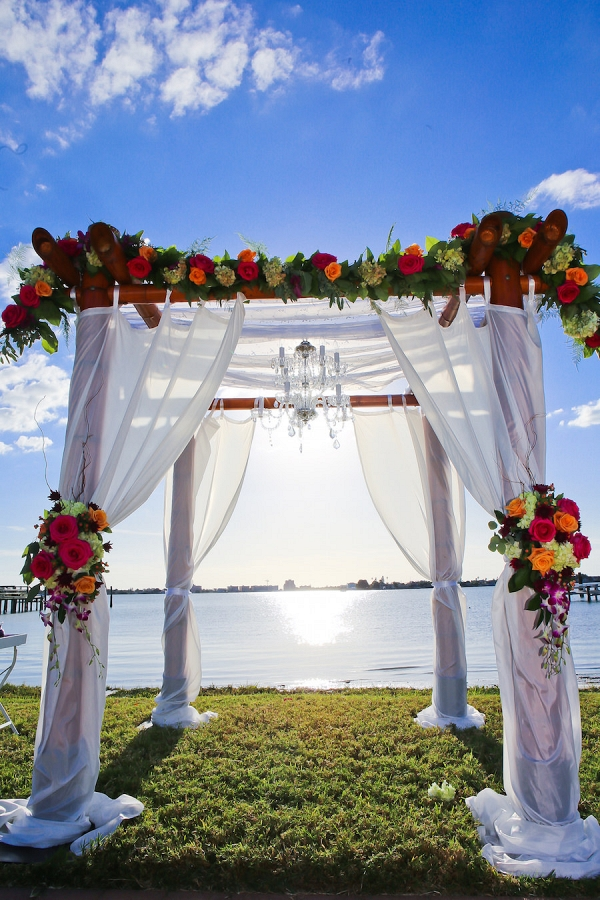 Waterfront Wedding Ceremony under Floral Arch with Fuchsia and Orange Roses, Greenery and Tulle Overlay