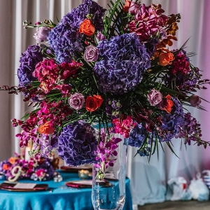 Tall Purple, Orange and Magenta Wedding Centerpiece Flowers in Glass Vase on Teal Linens