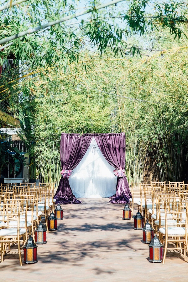 Outdoor Florida Wedding Ceremony with Purple Linen Flocked Archway and Gold Chaivari Chairs
