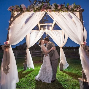 Nighttime, Twilight Bride and Groom Outdoor Wedding Portrait under Wedding Altar