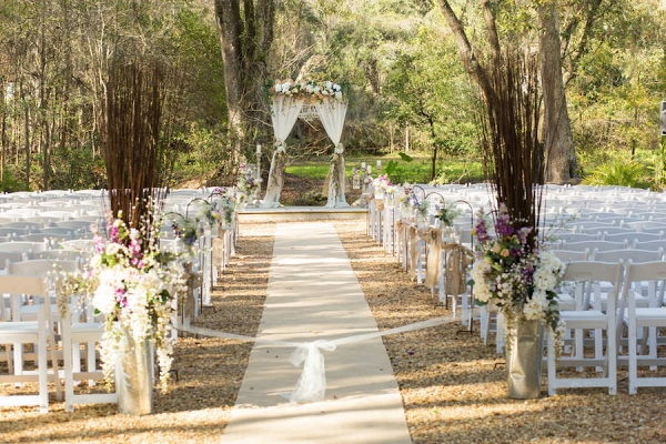 Outdoor, Rustic Wedding Ceremony Decor with Tall, Purple and Ivory Floral Aisle Decorations and Wooden Altar Decorated with Flowers