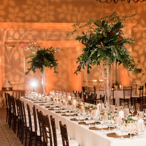 Indoor, Ballroom Wedding Reception Decor with Tall, Greenery Centerpieces in Glass Vases, Bamboo Chiavari Chairs, and Candlelight