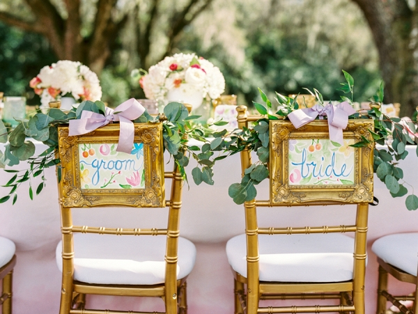 Outdoor Wedding Reception Seating with Watercolor Bride and Groom Chair Signs with Greenery with Gold Chiavari Chairs