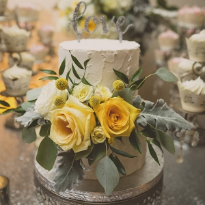Two Tier Round White Wedding Cake with Yellow Roses and Greenery on Silver Cake Stand with Love Cake Toppe