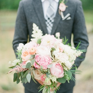 Groom in a gray suit holds a pink and white wedding bouquet