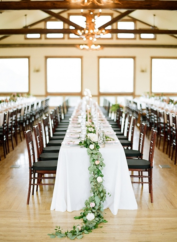 Long wedding tables with floral and greenery centerpiece runners