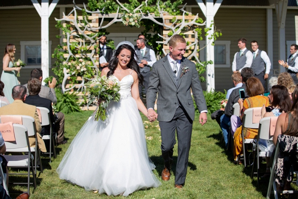 Rustic outdoor wedding ceremony with antler backdrop