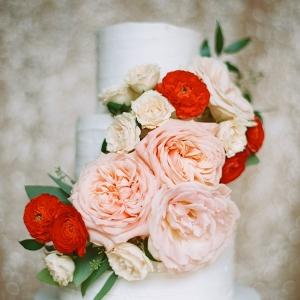 White Wedding Cake with Pink Cabbage Roses and Red Ranunculous