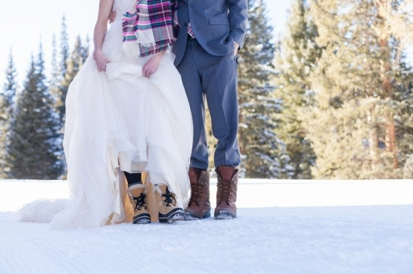 Bride and groom standing on the snow in their bridal attire and snow boots