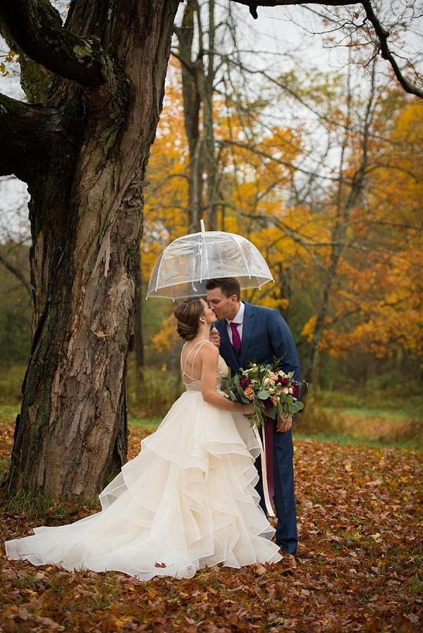 Romantic kiss under an umbrella on a beautiful autumn day