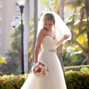 Classic destination wedding bride wearing a veil, Amsale wedding dress and Nina sash
