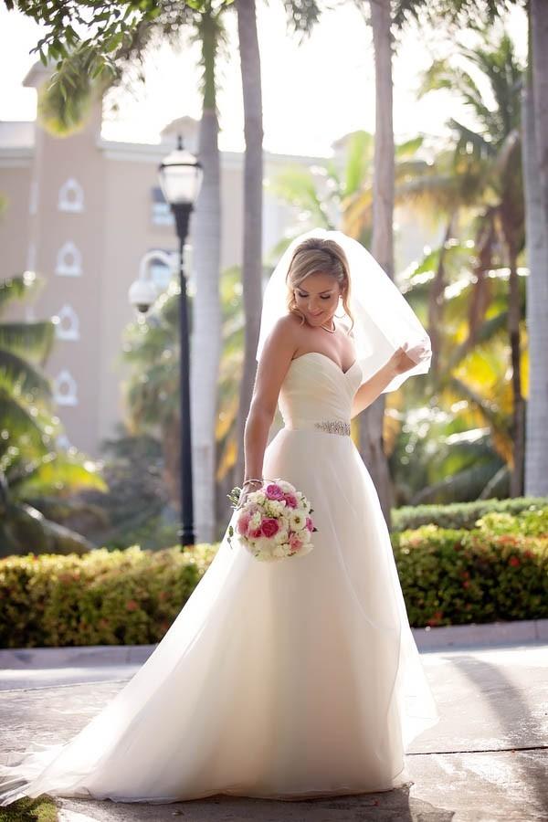 Classic destination wedding bride wearing a veil, Amsale wedding dress and Nina sash
