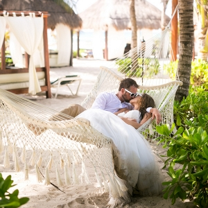 Bride and groom kissing in hammock