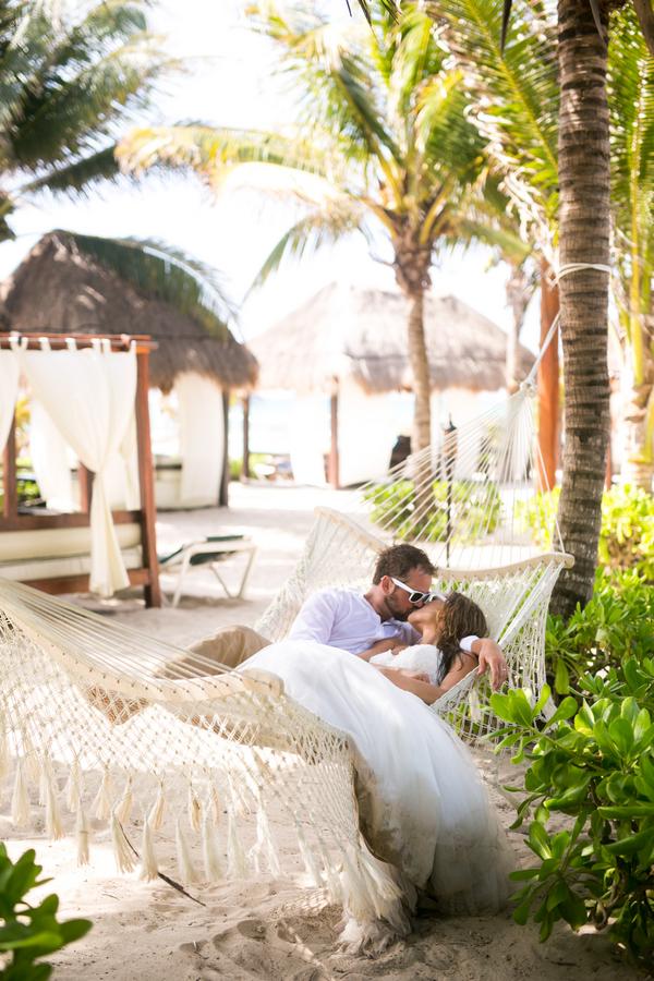 Bride and groom kissing in hammock