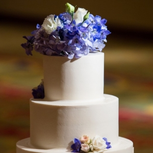 Elegant 3-tier wedding cake with floral topper and fondant cityscape