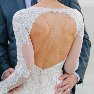 Gorgeous backless wedding dress with illusion lace paired with a simple backwards necklace