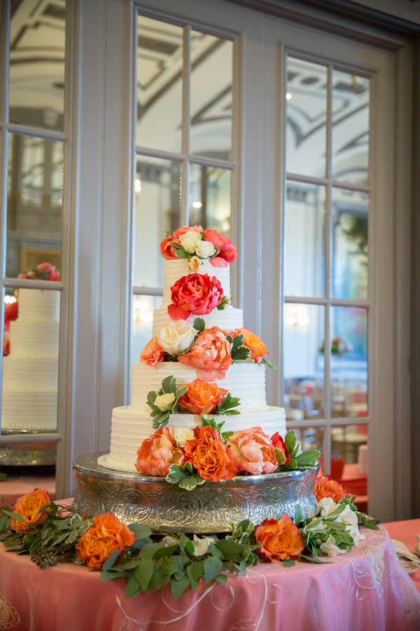 Gorgeous 4-tier wedding cake with coral and watermelon peonies and seeded eucalyptus