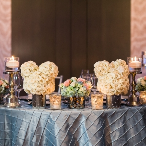 Sweetheart table with Mickey Mouse ear topiaries, candles and small floral arrangements