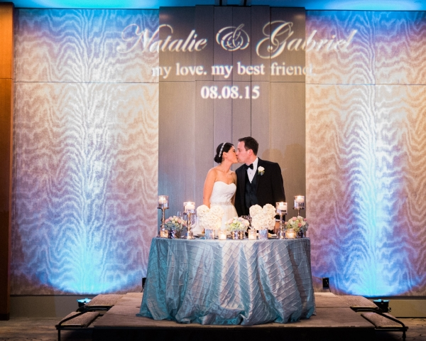Bride and groom kissing at their sweetheart table with blue uplighting