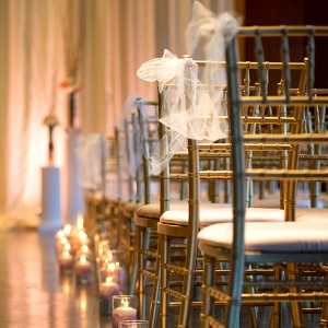 Adorably decorated chiavari chairs with tulle ribbon and a floating candle and flower petal lined aisle