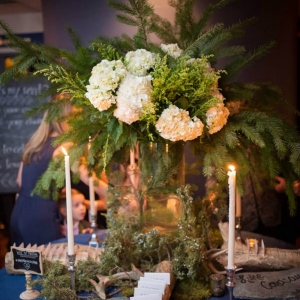 Enchanted forest escort card display with wooden logs, moss and pine branches