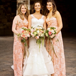 Floor length peach bridesmaid dresses with floral patterns by Amsale