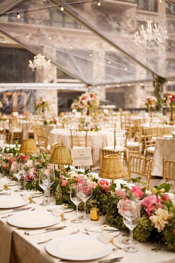 Romantic tented wedding tablescape with a lush floral table runner, gold lamps, and chiavari chairs