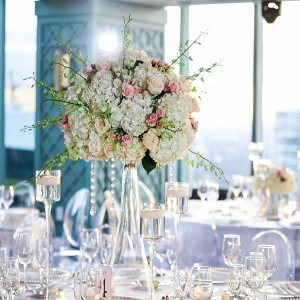 Glamorous wedding reception with tall centerpieces, clear chargers, crystal details and ghost chairs