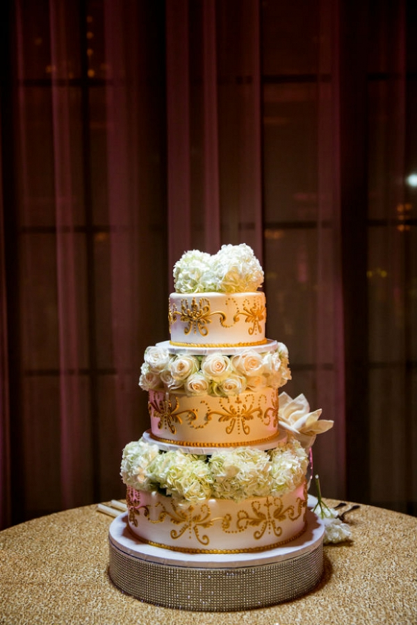 Versailles inspired wedding cake with gold piped details, rose and hydrangea layers, and a rhinestone cake stand