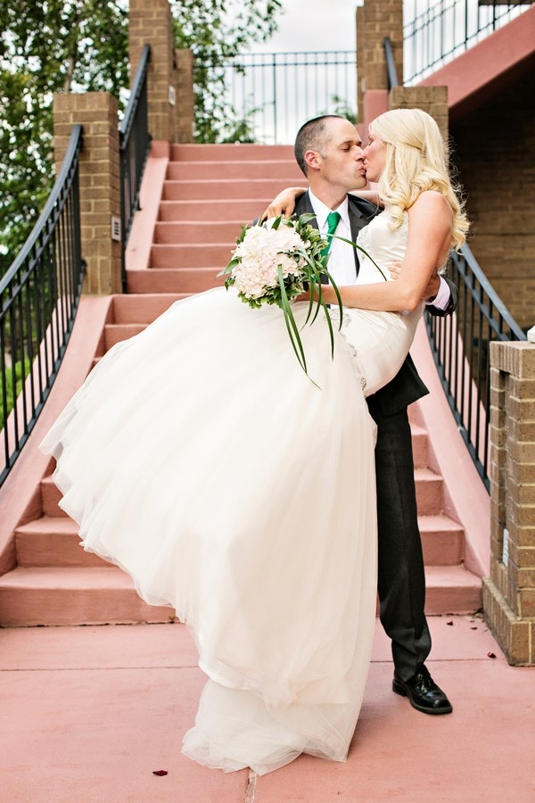 Portrait of groom holding bride and kissing